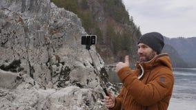 O turista farpado está tendo a videoconferência com amigos em um telefone celular no banco de um rio da montanha Movimento lento video estoque