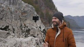 O turista farpado está transmitindo o vídeo em um telefone celular no banco de um rio da montanha Movimento lento vídeos de arquivo