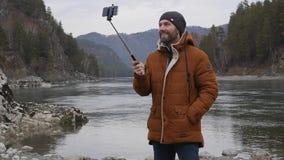 O turista farpado está transmitindo o vídeo em um telefone celular no banco de um rio da montanha Movimento lento filme