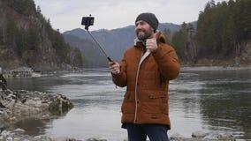 O turista farpado fotografa-se em um telefone celular no banco de um rio da montanha Movimento lento vídeos de arquivo