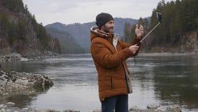 O turista farpado fotografa-se em um telefone celular no banco de um rio da montanha Movimento lento filme