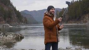O turista farpado fotografa-se em um telefone celular no banco de um rio da montanha Movimento lento video estoque