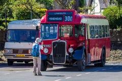 O turista faz uma fotografia de um ônibus inglês velho Fotos de Stock Royalty Free