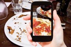 O turista fotografa a pizza italiana com presunto de parma fotografia de stock royalty free