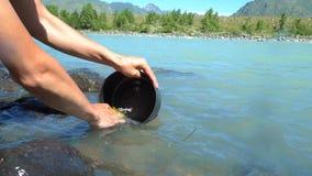 O turista lava os pratos no rio video estoque
