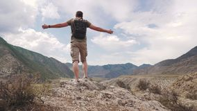 O turista levanta suas mãos acima na borda do penhasco Um viajante do homem aprecia o objetivo conseguido e aprecia a vitória filme