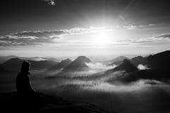 O turista longo novo bonito da menina do cabelo aprecia a aurora no canto afiado da rocha do arenito e olha-a sobre o vale a Sun imagem de stock