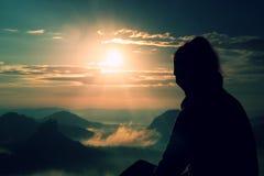 O turista longo novo bonito da menina do cabelo aprecia a aurora no canto afiado da rocha do arenito e olha-a sobre o vale a Sun fotos de stock