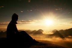 O turista longo novo bonito da menina do cabelo aprecia a aurora no canto afiado da rocha do arenito e olha-a sobre o vale a Sun foto de stock