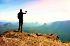O turista magro na borda da rocha no parque dos impérios da rocha está olhando sobre o vale enevoado e nevoento da manhã a Sun foto de stock royalty free
