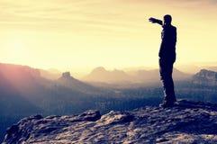 O turista magro no pico afiado da rocha no parque dos impérios da rocha está olhando sobre o vale enevoado e nevoento a Sun foto de stock royalty free