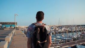 O turista masculino está apreciando uma caminhada no cais do mar com os iate na manhã ensolarada vídeos de arquivo