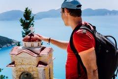 O turista masculino toca em pensativo ao santuário helênico pequeno Proskinitari, Grécia Opinião surpreendente do mar no fundo fotografia de stock