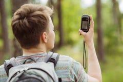 O turista nas madeiras determina o lugar usando gps Imagem de Stock Royalty Free