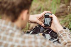 O turista nas madeiras determina o lugar usando gps Fotos de Stock Royalty Free