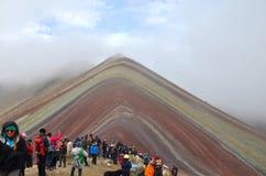 O turista obt?m um relance da montanha do arco-?ris de Vinicunca no Peru atrav?s das nuvens imagens de stock