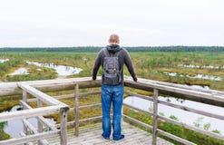 O turista parou na ponte com trouxa para apreciar a natureza no dia de verão imagens de stock