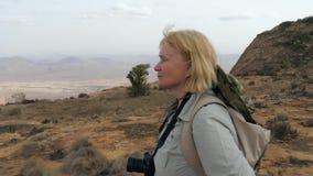 O turista parou para relaxar na elevação nas montanhas e admira o cenário video estoque