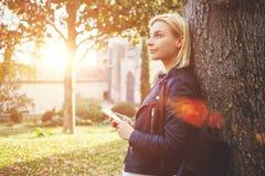 O turista pensativo da mulher está guardando o telefone esperto, quando apreciar o tempo livre nas férias Imagens de Stock Royalty Free