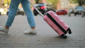 O turista que irreconhec?vel a mulher rola uma mala de viagem vai ao longo do passeio na cidade vídeos de arquivo