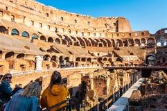 O turista que olha o Colosseum ou o coliseu famoso, igualmente conhecido como Flavian Amphitheatre, é um anfiteatro oval no centr imagem de stock