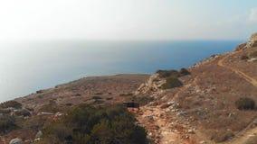 O turista senta-se em um banco no lado de uma montanha e da vista na distância, no fundo do mar bonito filme