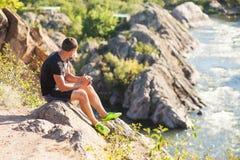 O turista senta-se em uma rocha e olha-se um rio da montanha Imagens de Stock