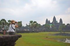 O turista senta-se na pedra grande para fotografar o templo de Preah Vihear Imagens de Stock Royalty Free