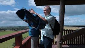 O turista toma imagens na torre da vista perto dos binóculos filme
