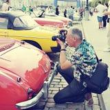 O turista toma uma imagem de um carro do vintage Fotos de Stock Royalty Free