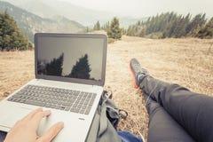 O turista usa o portátil remotamente e relaxa na montanha Fotos de Stock Royalty Free
