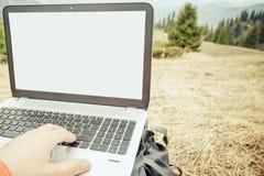 O turista usa o portátil remotamente e relaxa na montanha Foto de Stock
