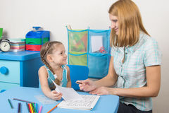 O tutor de cinco anos da menina mostra a tarefa terminada em uma folha Fotografia de Stock Royalty Free