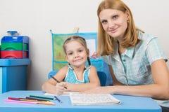 O tutor e a menina idosa de cinco anos contrataram na soletração Foto de Stock