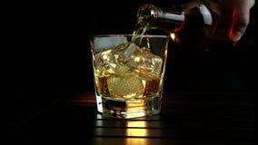 O uísque de derramamento do empregado de bar no vidro com os cubos de gelo na tabela de madeira e no fundo escuro preto, foco em  vídeos de arquivo