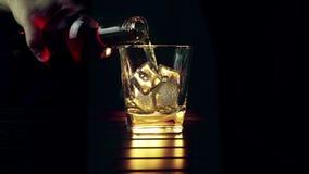 O uísque de derramamento do empregado de bar no vidro com os cubos de gelo na tabela de madeira e no fundo escuro preto, foco em  filme