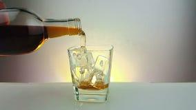 O uísque de derramamento do empregado de bar com a garrafa no vidro bebendo com os cubos de gelo no fundo branco morno, época de  filme