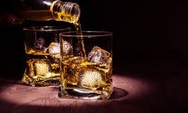 O uísque de derramamento do empregado de bar nos vidros na tabela de madeira, atmosfera morna, estilo antigo, época de relaxa com imagem de stock