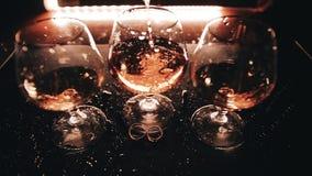 O uísque derrama belamente em um dos três vidros que estão na tabela Muito close-up Luz bonita filme