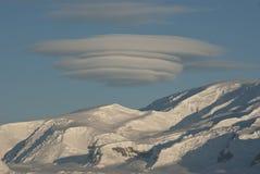 O UFO incomum deu forma à nuvem sobre o dia de inverno antárctico das montanhas Imagens de Stock