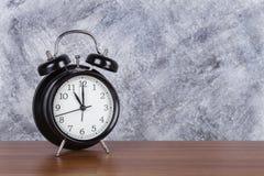 11 O-` Uhr-Weinleseuhr auf hölzernem Tabellen- und Wandhintergrund Lizenzfreie Stockfotografie