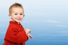 O um anos de idade adoráveis na camisola vermelha no céu azul Fotos de Stock