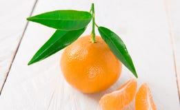 O um mandarino no fundo de madeira branco Imagens de Stock Royalty Free