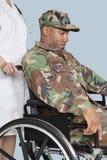 O uniforme vestindo da camuflagem do soldado triste dos E.U. Marine Corps na cadeira de rodas ajudou pela enfermeira fêmea Fotografia de Stock Royalty Free