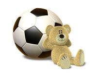 O urso de Nhi inclina-se de encontro à esfera de futebol Imagem de Stock