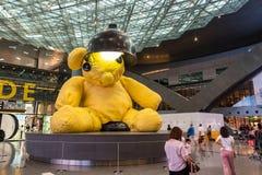O urso de peluche amarelo grande da lâmpada no meio do terminal em Foto de Stock Royalty Free