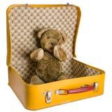 O urso de peluche antigo que senta-se em uma mala de viagem amarela quer viajar Imagem de Stock