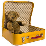 O urso de peluche antigo que senta-se em uma mala de viagem amarela quer viajar Imagem de Stock Royalty Free