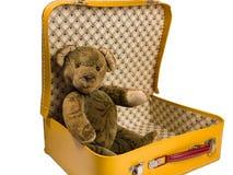 O urso de peluche antigo que senta-se em uma mala de viagem amarela quer viajar Imagens de Stock