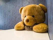O urso de peluche bonito senta-se na cadeira na frente da mesa de jantar Faça-o parecer como o prato favorito de espera fotografia de stock royalty free